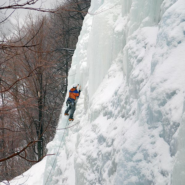 Ice climber ascending an ice wall