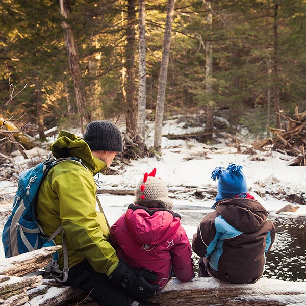 Father, daughter and son sitting by stream surrounded by snow