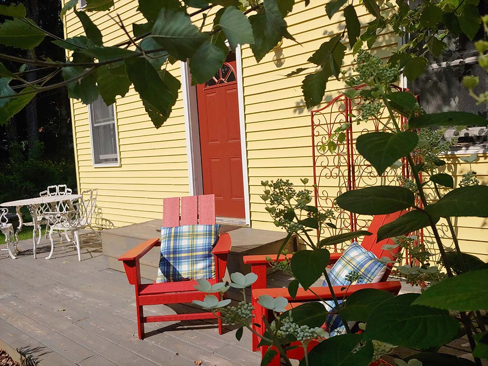 deck with 2 red Adirondack chairs