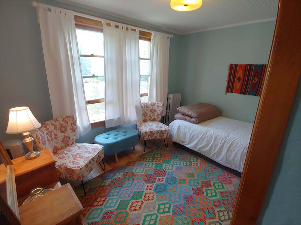 bedroom with twin bed and colorful rug